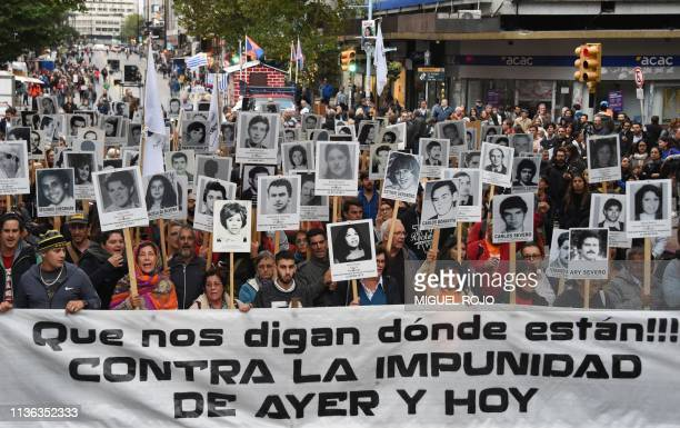 People hold pictures of missing relatives during a gathering called by trade unions and relatives of victims of the 19731985 dictatorship in Uruguay...