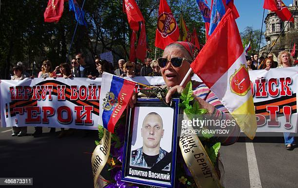 People hold pictures of policemen who died during anti-government protests in Kiev last winter, as they take part in a pro-Russia demonstration in...