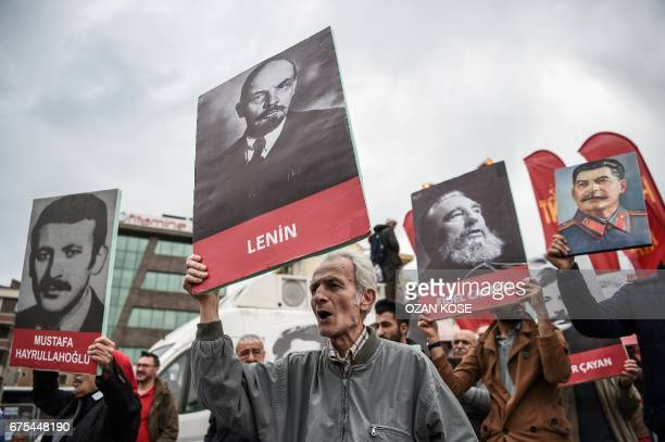 People hold placard picturing Mustafa Hayrullahoglu late member of the Socialist part Workers Party of Turkey Soviet leader Vladimir Ilitch Lenin...