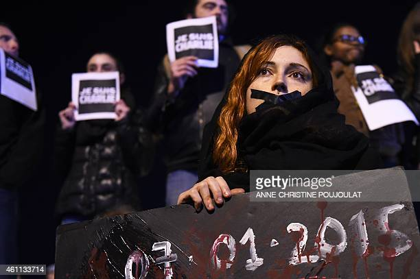 People hold placard reading 'I am Charlie' during a gathering on the Old Harbor in Marseille on January 7 following an attack by unknown gunmen on...
