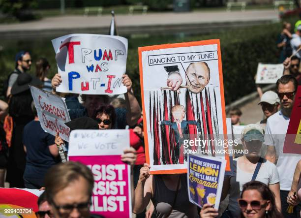 People hold placards and banners during the socalled 'Helsinki Calling' march towards the Senate Square to defend the human rights freedom of speech...