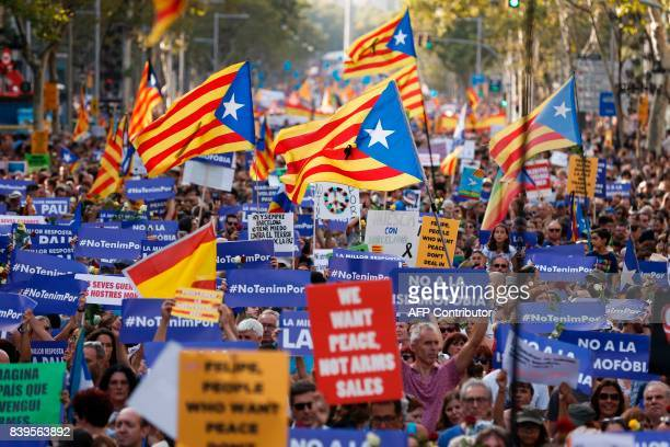 People hold placards and Catalan flags during a march against terrorism which slogan will be #NoTincPor in Barcelona on August 26 following the...