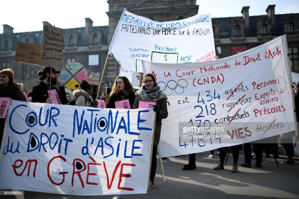 People hold placards and chant slogans during a gather called by the French Office for Refugees and Stateless Persons (OFPRA), to protest against the immigration law on February 21, 2018 in Paris. SAKUTIN