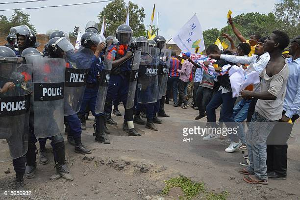 People hold placards and face Congolese antiriot policemen on October 19 2016 in Goma during a demonstration over plans by Democratic Republic of...