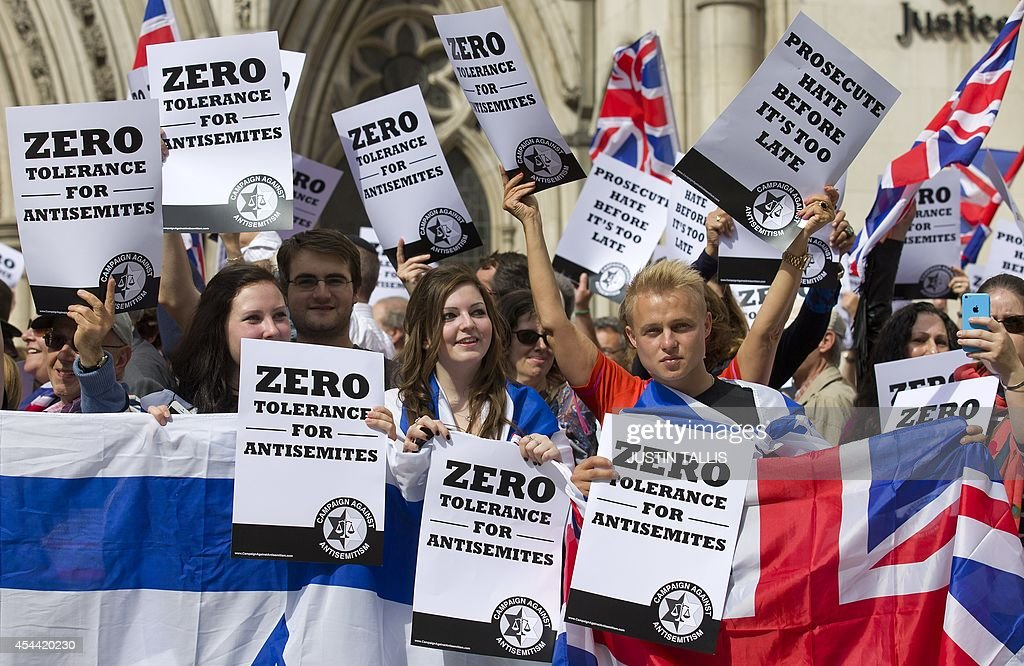 People hold placards and Israeli and Union flags outide the Royal Courts of Justice as Jewish groups rally in London on August 31, 2014, calling for 'Zero Tolerance for Anti-Semitism'. Jewish groups demonstrated outside the British High Court as latest figures published by the Community Security Trust reported a spike in anti-semitic attacks on people and property in the UK following the lastest outbreak of violence between Israel and Palestinians in Gaza.
