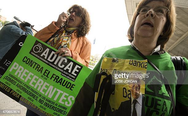 People hold placards and mask as they protest against fraud outside the building where is held the Bankia Shareholders Extraordinary General meeting...