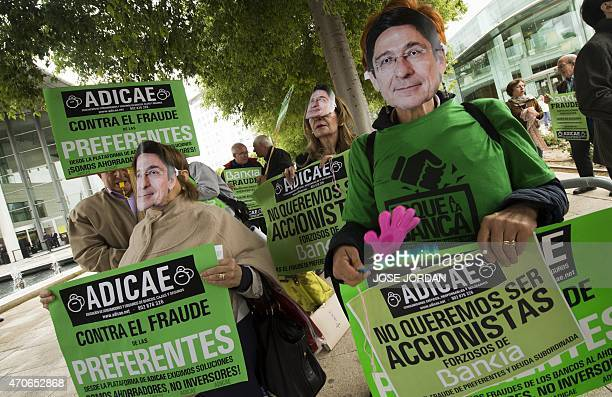 People hold placards and masks of Spanish bank Bankia president Jose Ignacio Goirigolzarri as they protest against fraud outside the building where...
