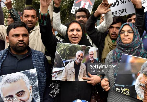 People hold placards and raise slogans during a protest against the killing of Iranian major general Qassim Soleimani near US high commission on...