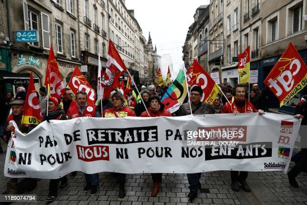 TOPSHOT People hold placards and wave flags of different French national trade unions as they take part in a demonstration in Caen on December 17...
