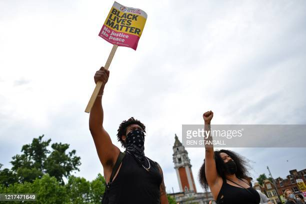 People hold placards as they gather for an antiracism demonstration in Windrush Square Brixton in south London on June 3 after George Floyd an...