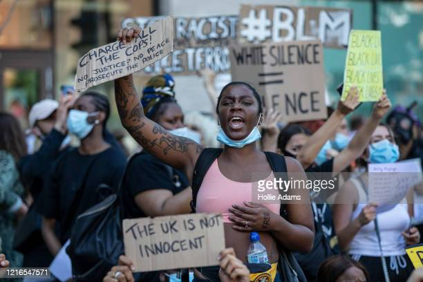People hold placards as they join a spontaneous Black Lives Matter march through central London to protest the death of George Floyd in Minneapolis...