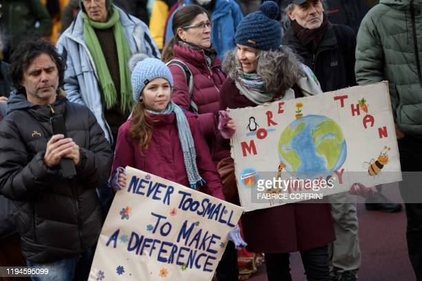 People hold placards as they take part in a gathering called by climate activists prior to the start of a march to Davos ahead of the World Economic...