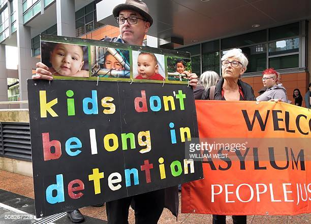 People hold placards at a protest outside an immigration office in Sydney on February 4 as Australian church leaders said they would offer sanctuary...