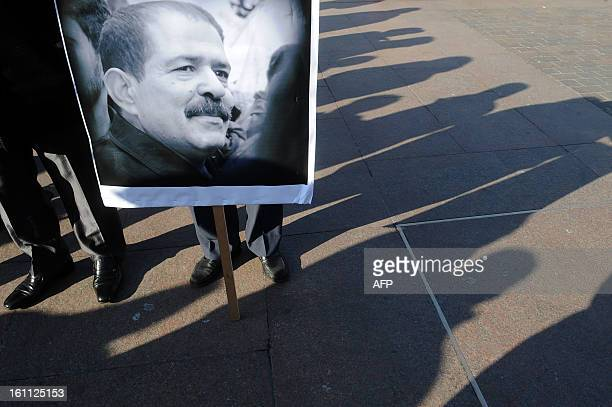 People hold placards bearing portraits of murdered opposition figure Chokri Belaid during a protest to pay tribute to Belaid on February 9 in...