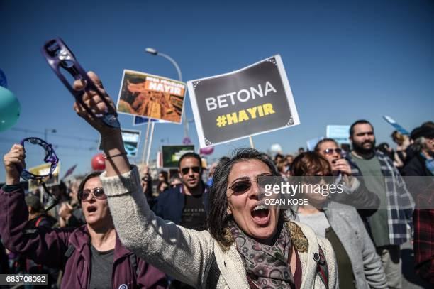 People hold placards calling Turkish voters to vote 'no' on the upcoming referendum as they shout slogans while they march over the Galata bridge on...