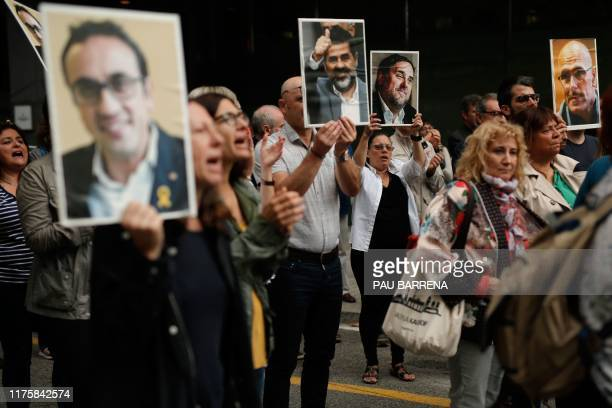 People hold placards depecting pictures of jailed Catalan separatist leaders in Barcelona on October 14 after Spain's Supreme Court sentenced nine...
