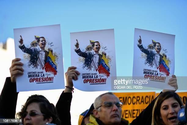 TOPSHOT People hold placards depecting the president of Venezuela's oppositionled National Assembly Juan Guaido and reading Scream with energy Death...