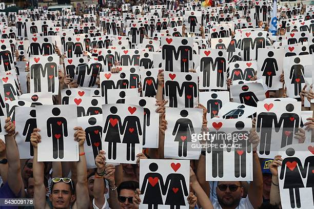 People hold placards depicting hearts and couples, during a flash mob for the annual Lesbian, Gay, Bisexual and Transgender Pride Parade in Milan, on...