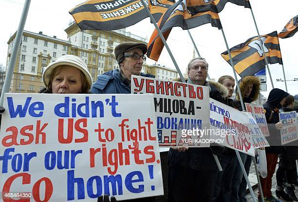 People hold placards during a protest against USA international policy in front of US embassy in central Moscow on March 7 2015 EU foreign ministers...