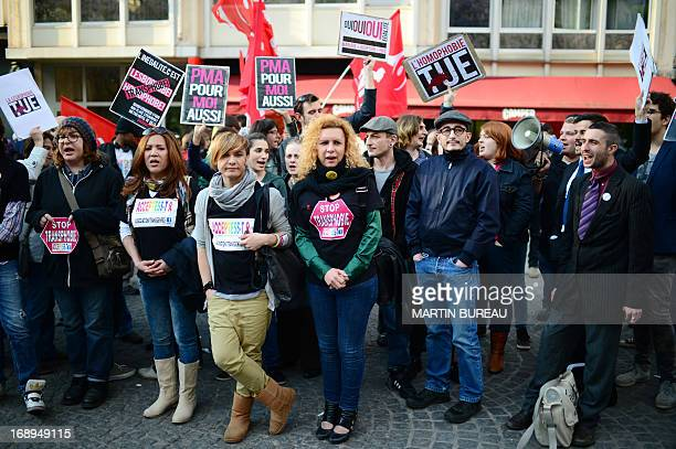 People hold placards during a protest called by Act Up gay organisation on May 17 2013 in Paris as part of the International Day Against Homophobia...