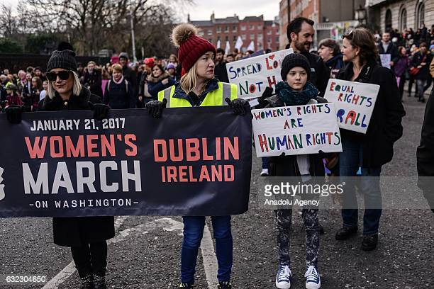 People hold placards during a protest held in solidarity with the Washington DC Women's March in Dublin Ireland on January 21 2017