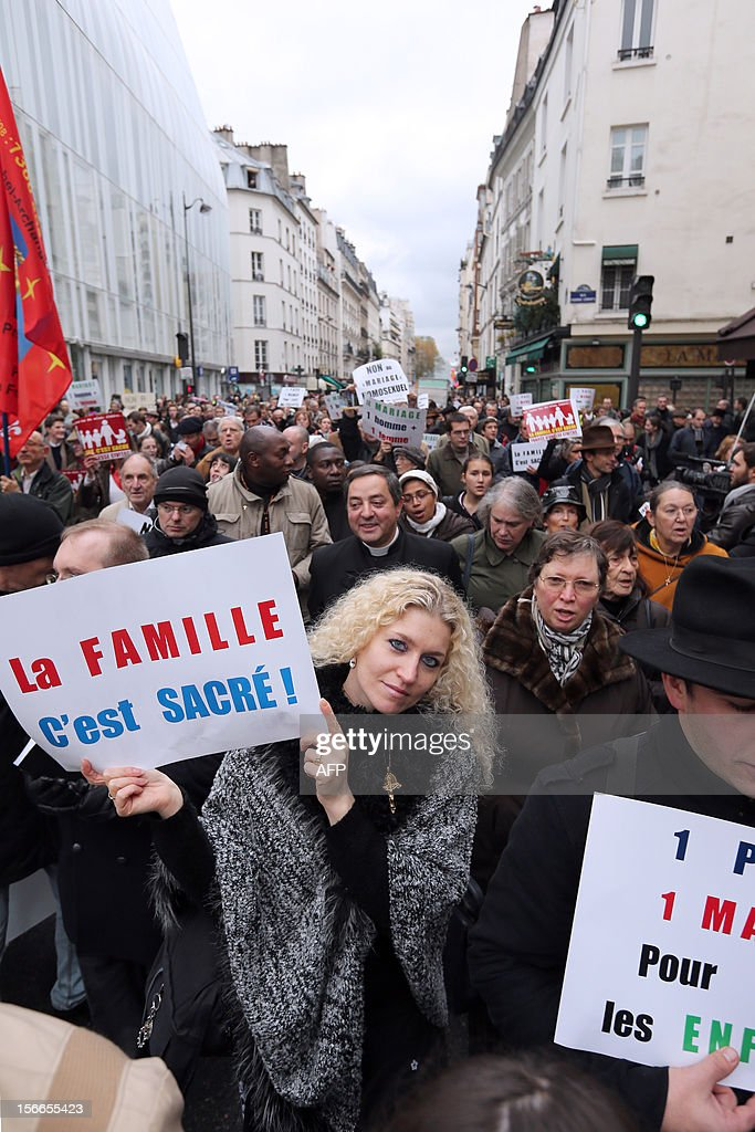 People hold placards during a protest organized by fundamentalist Christians group Civitas Institute against the same-sex marriage on November 18, 2012 in Paris. France's Socialist government on November 7, 2012 adopted a draft law to authorise gay marriage and adoption despite fierce opposition from the Roman Catholic Church and the right-wing opposition.