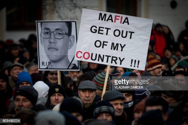 TOPSHOT People hold placards during a silent protest march in memory of murdered journalist Jan Kuciak and his girlfriend Martina Kusnirova in...