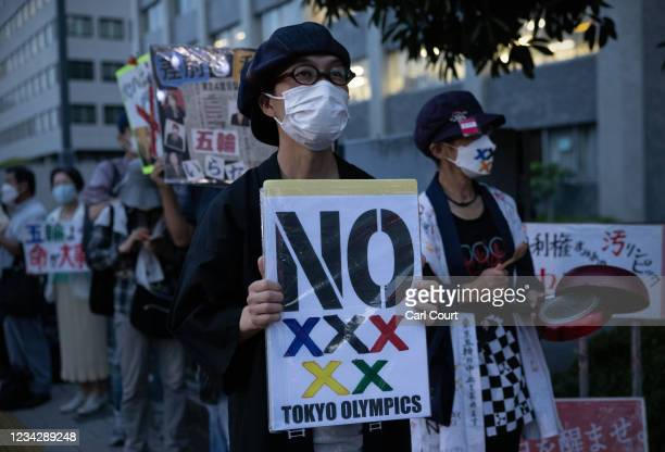 People hold placards during an anti-Olympics protest outside the official residence of Japans Prime Minister, Yoshihide Suga, on July 29, 2021 in...