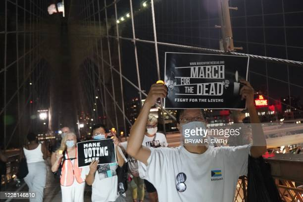"""People hold placards during the """"March for the Dead"""" across the Brooklyn Bridge, in memory of those who have died of COVID-19 and to protest the..."""