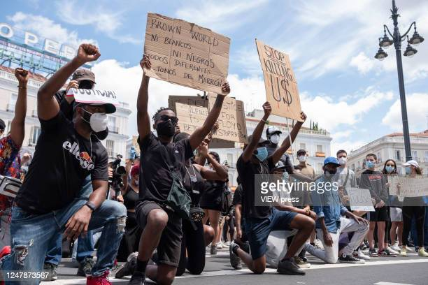 People hold placards in Puerta del Sol during the demonstration organized in support of George Floyd and against racism on June 07 2020, in Madrid,...