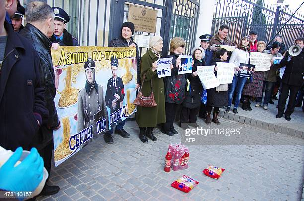 """People hold placards portraying Russian President Vladimir Putin as a German SS officer and signed """"Putin's noodles"""" and """"We are fools"""" during a..."""