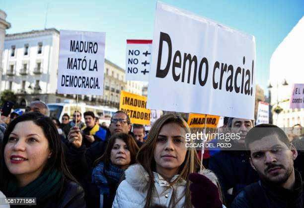 People hold placards reading Democracy and Maduro killed Democracy during a demonstration called by Venezuelan citizens against President Nicolas...