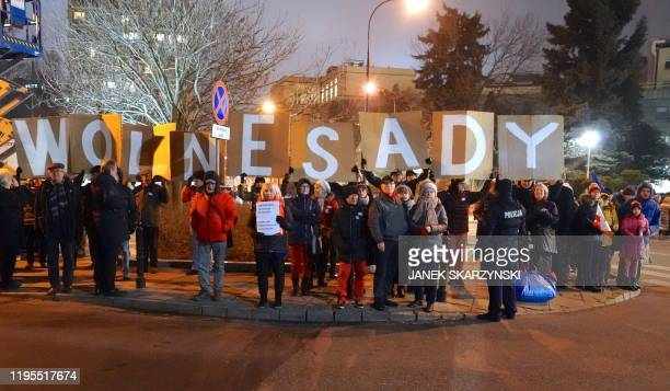 """People hold placards reading """"free zones"""" during a demonstration in front of Polish parliament against a judicial reform pushed by lawmakers of the..."""