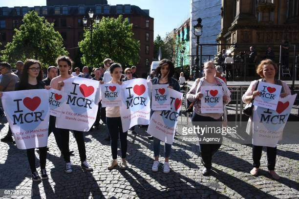 People hold placards reading 'I love Manchester' as they take part in a commemoration ceremony held for explosion victims of Manchester Arena stadium...