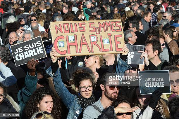 People hold placards reading 'je suis Charlie' and 'we all are Charlie' during a demonstration attended by an estimated 45000 in Marseille...