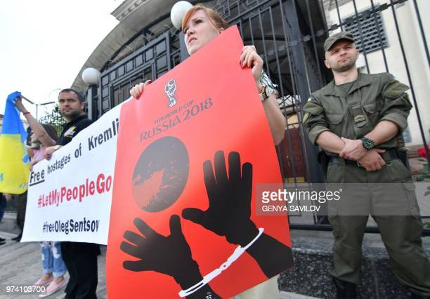 People hold placards with an appeal to boycott the Russia World Cup 2018 football tournament in front of the Russian Embassy in Kiev on June 14...