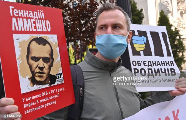"""People hold placards with portraits of Ukrainian citizens jailed in Crimea and Russia during their action """"Mr. President, talk to us"""" outside the..."""