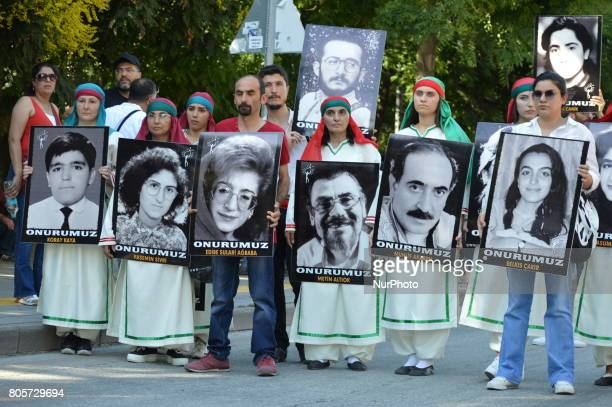 People hold portraits during a march to the 24th anniversary of the Sivas massacre in Ankara on July 02, 2017. In 1993, 35 people were killed after a...