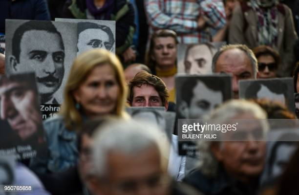 People hold portraits of Armenian intellectuals who were detained and deported in 1915 during a rally on Istiklal Avenue in Istanbul on April 24 held...
