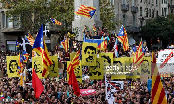 """People hold portraits of jailed Catalan separatists and Catalan pro-independence """"estelada"""" flags following a week of protests over the jail..."""