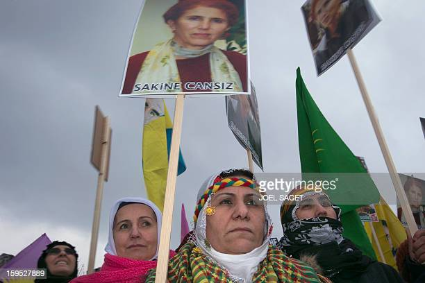 People hold portraits of late Kurdistan Workers' Party cofounder Sakine Cansiz on january 15 2013 in the parisian suburban city of Villiers leBel...
