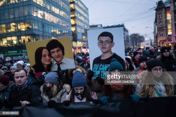 People hold portraits of murdered Slovak journalist Jan Kuciak and his girlfriend Martina Kusnirova during a silent protest march in their memory on...