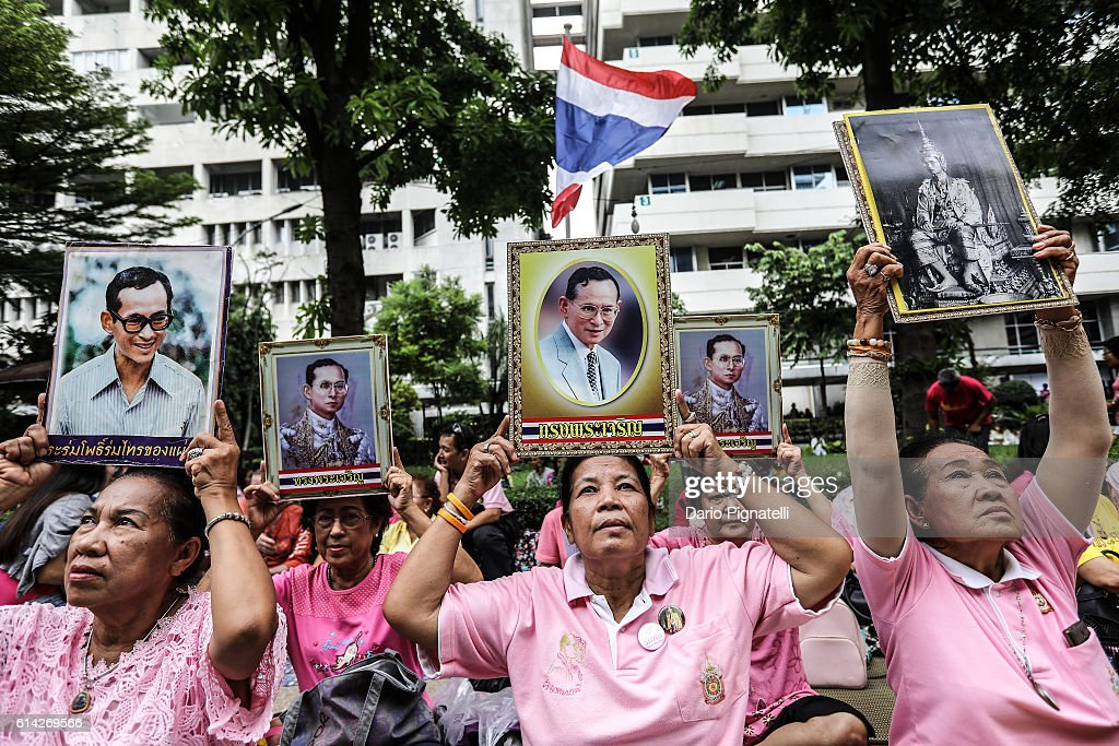 People hold portraits of Thai King Bhumibol Adulyadej as they participate to prayers for his health at Siriraj hospital, on June 13, 2016 in Bangkok, Thailand. The health of Thailand's 88-year-old king has deteriorated and is in an 'unstable condition' as hundreds of anxious supporters gather at Bangkok's Siriraj Hospital to continue their prayers for their ailing King Bhumibol Adulyadej.