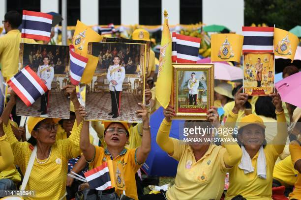 People hold portraits of Thailand's King Maha Vajiralongkorn as they wait for him and Thailand's Queen Suthida to appear at the balcony of...