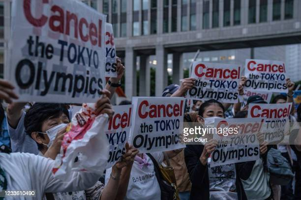 People hold posters during a protest against the Olympic Games on June 23, 2021 in Tokyo, Japan. Protests have continued to take place in the run up...