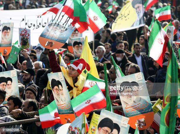 People hold posters of 1st Supreme Leader of Iran Ruhollah Khomeini and 2nd Supreme Leader of Iran Ali Khamenei and Iranian flags during a ceremony...