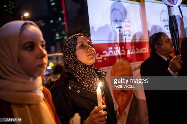 People hold posters picturing Saudi journalist Jamal Khashoggi and lightened candles during a gathering outside the Saudi Arabia consulate in...