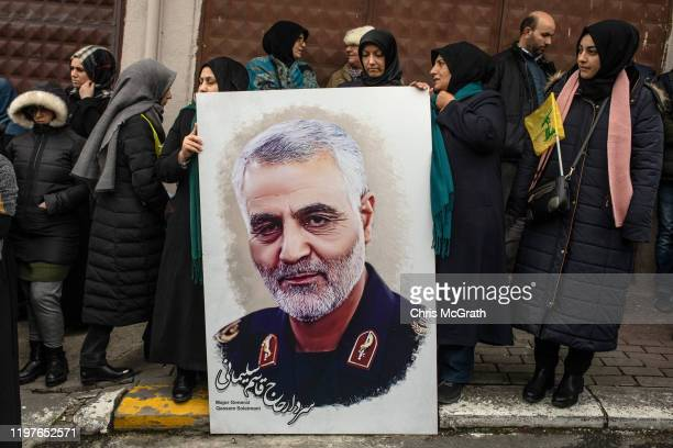 People hold posters showing the portrait of Iranian Revolutionary Guard Major General Qassem Soleimani and chant slogans during a protest outside the...