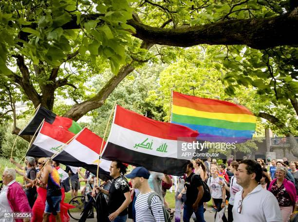 People hold rainbow and Iraqi flags during the Pride Walk through the center of Amsterdam on July 29 2017 The march marks the beginning of Pride...