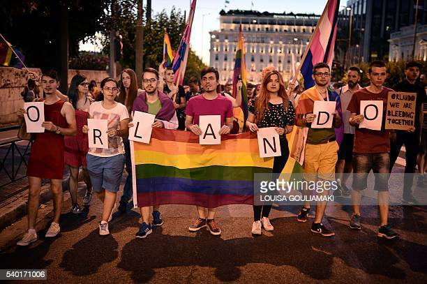 People hold rainbow flags and letter which say ORLANDO during a march organised by the Greek LGBTQ community on June 14 2016 in Athens to pay tribute...